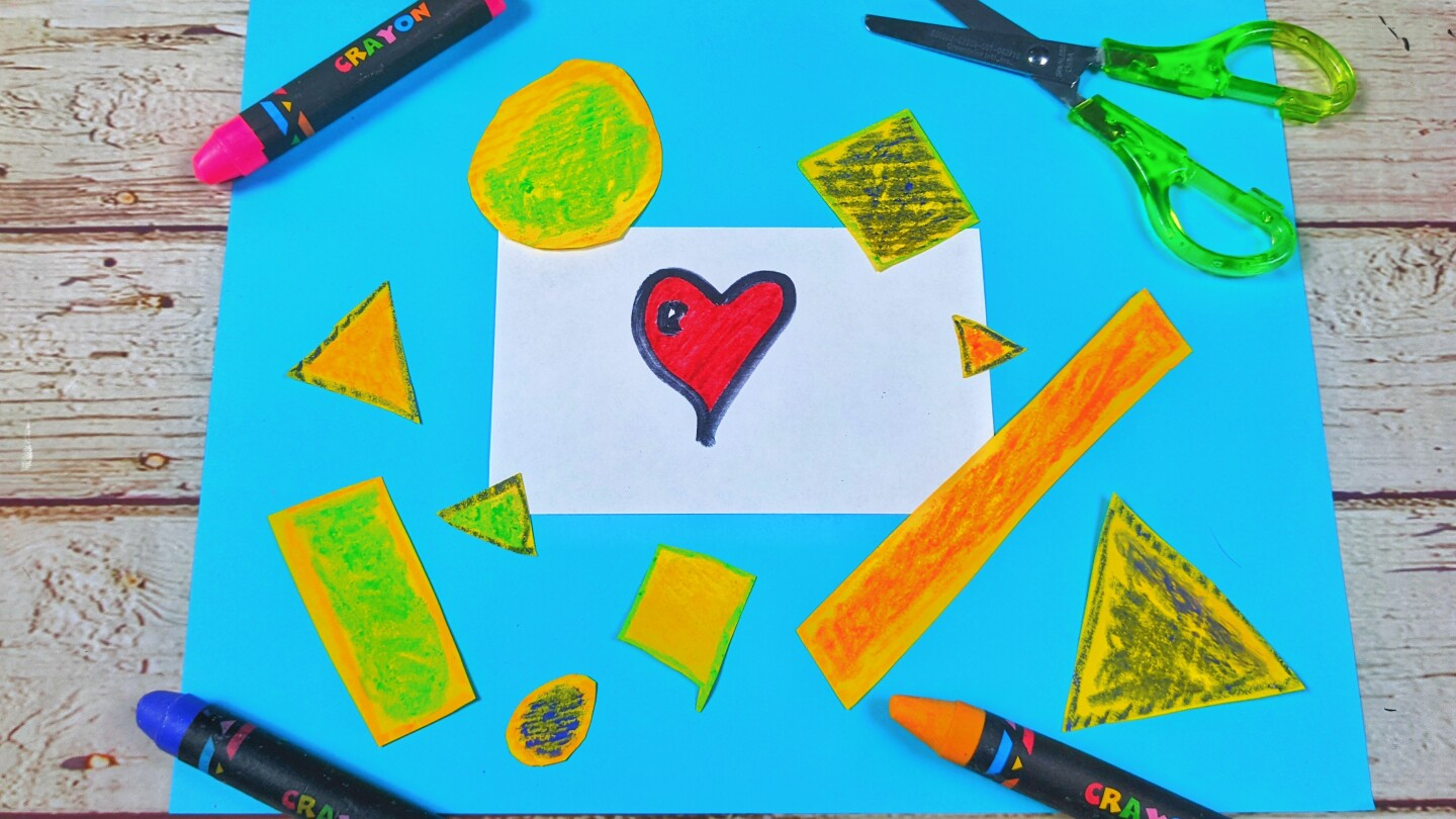 A sheet of blue paper with colorful cut outs of different shapes on it surrounded by crayons and a pair of green scissors.