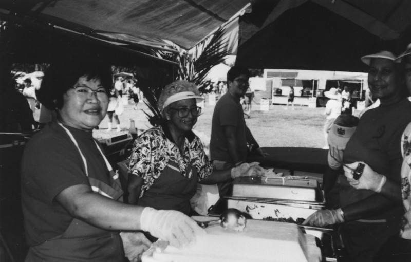Black and white photo of food servers as they pause in their work to smile at the camera at the Hawaiian Civic Club Festival, 1992