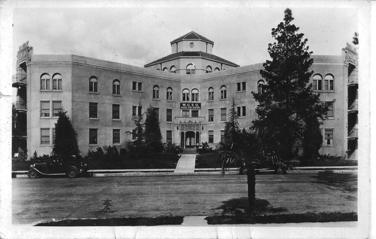 A black and white postcard photo of the Woman's Christian Temperance Union Home in Eagle Rock probably taken a few years after the home opened in 1928. The four-story main building is in the shape of a Maltese cross with Churrigueresque ornamentation over the main door, an the elevator in the center and four wings reaching out.