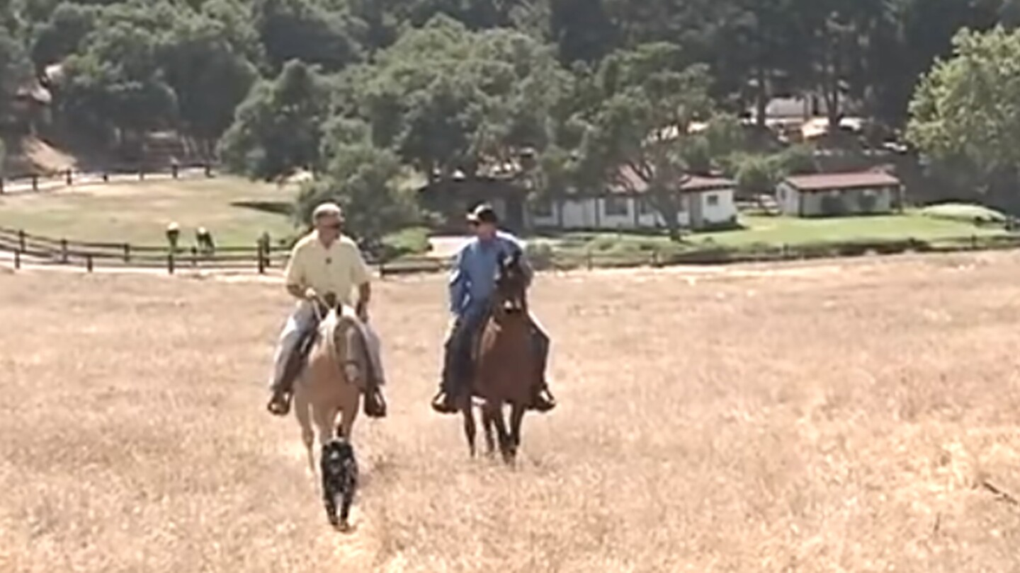 "Huell Howser rides on a horse in a dry field | From ""Reagan Ranch"""