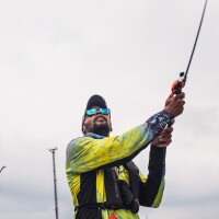 A man casts a fishing line. Behind him is a gloomy, gray-blue sky. The man is wearing sunglasses with teal blue lenses and a bright yellow jacket.