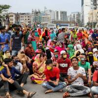 Garments workers shout slogans as they block a road demanding their due wages during the lockdown amid concerns over the coronavirus disease (COVID-19) outbreak in Dhaka, Bangladesh, April 15, 2020. | REUTERS/Mohammad Ponir Hossain