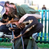 A homeless man named Shaggy cozies up with his dog, 2Toes, on a park bench in Santa Monica. | photo Luis Sinco/Los Angeles Times via Getty Images
