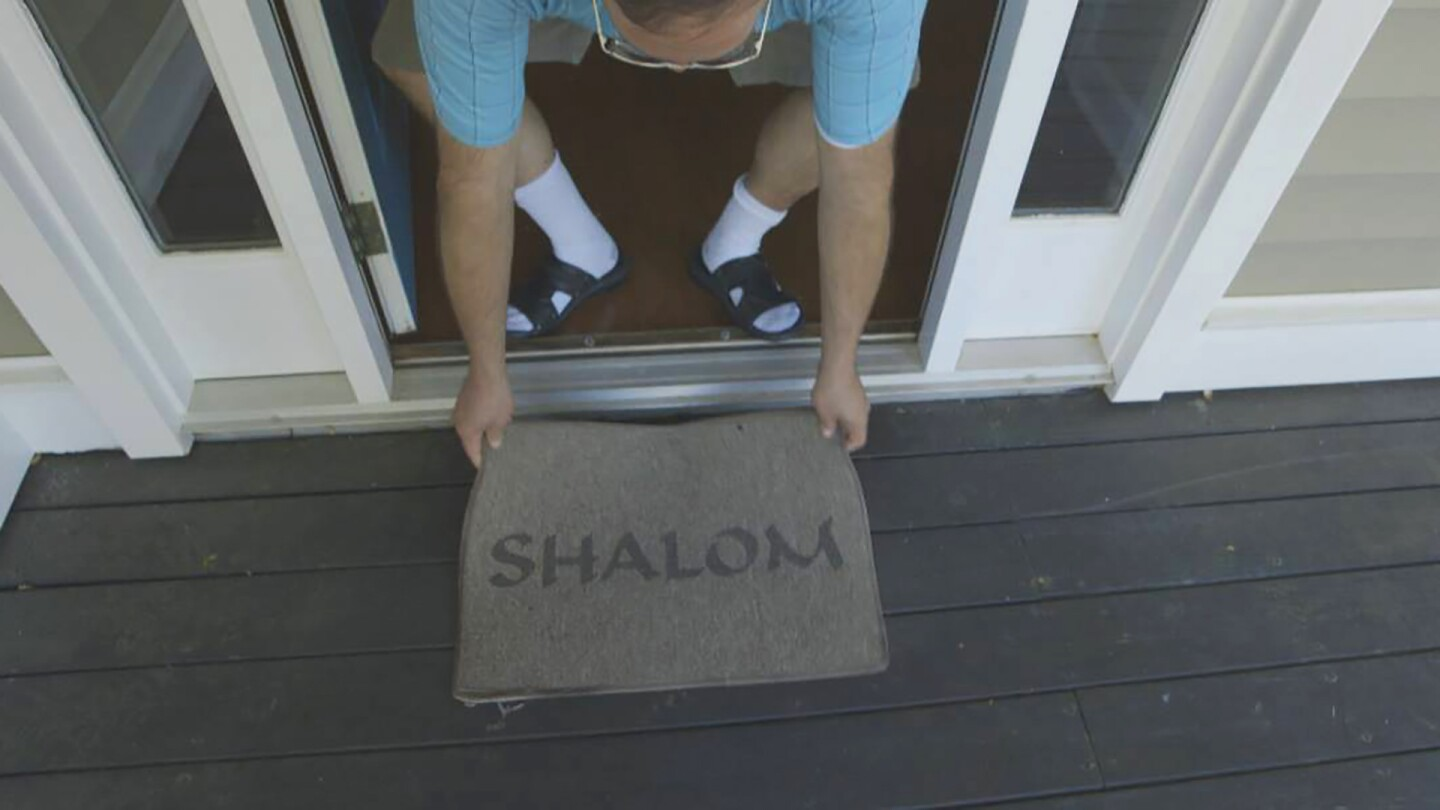 "Terence places ""Shalom"" Welcome Mat at new home. 