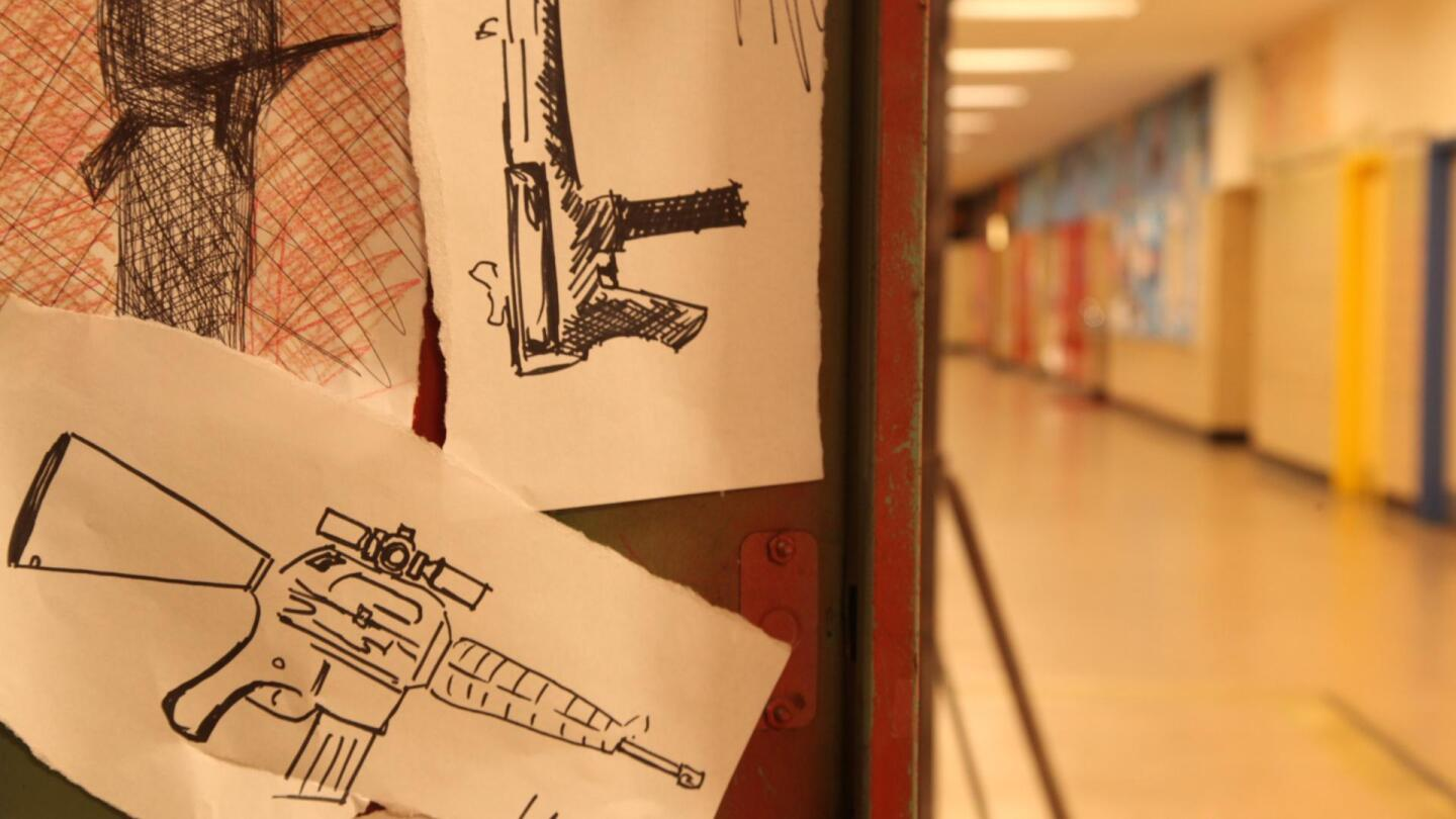 Drawings of assault rifles tacked on the walls of a school.