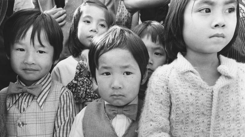 Close-up, black and white photo of a group of Vietnamese American children.
