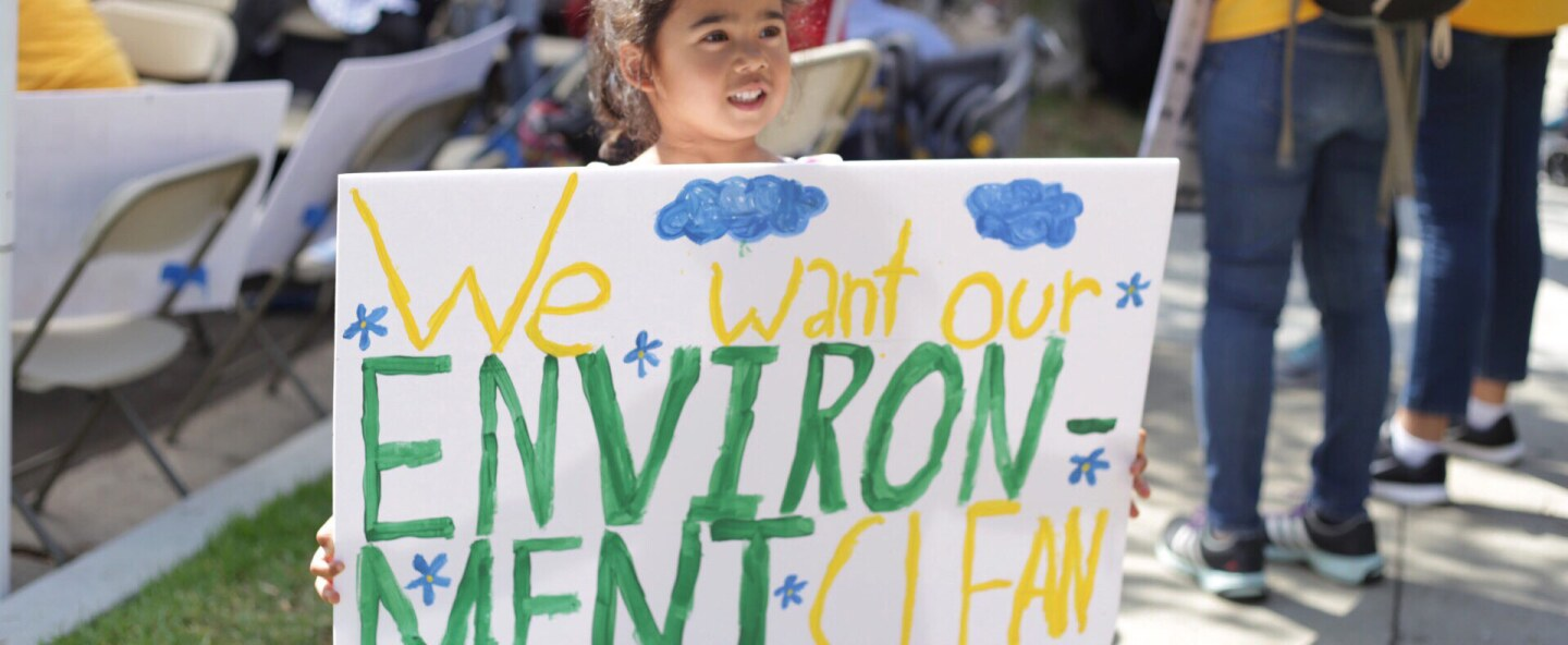 """A small child holds a sign up at a protest. It reads """"We want our ENVIRONMENT CLEAN."""""""