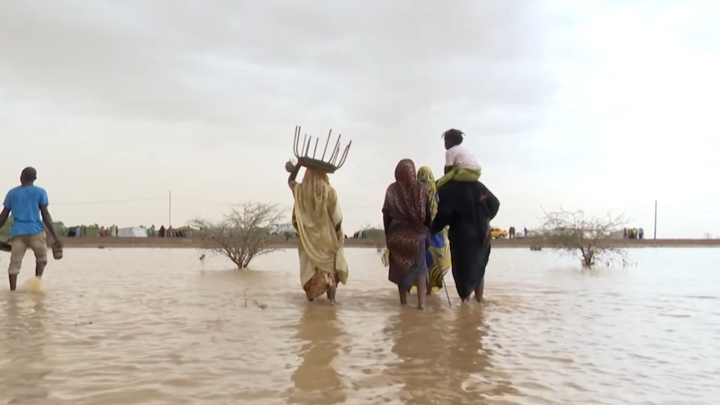 A group of people wade through flood waters.