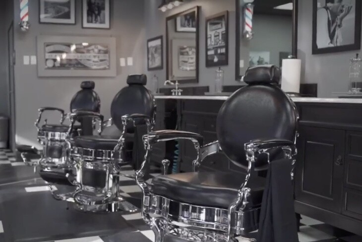 A screenshot shows the empty interior of Barberhood in a promotional video on their site about the reopening