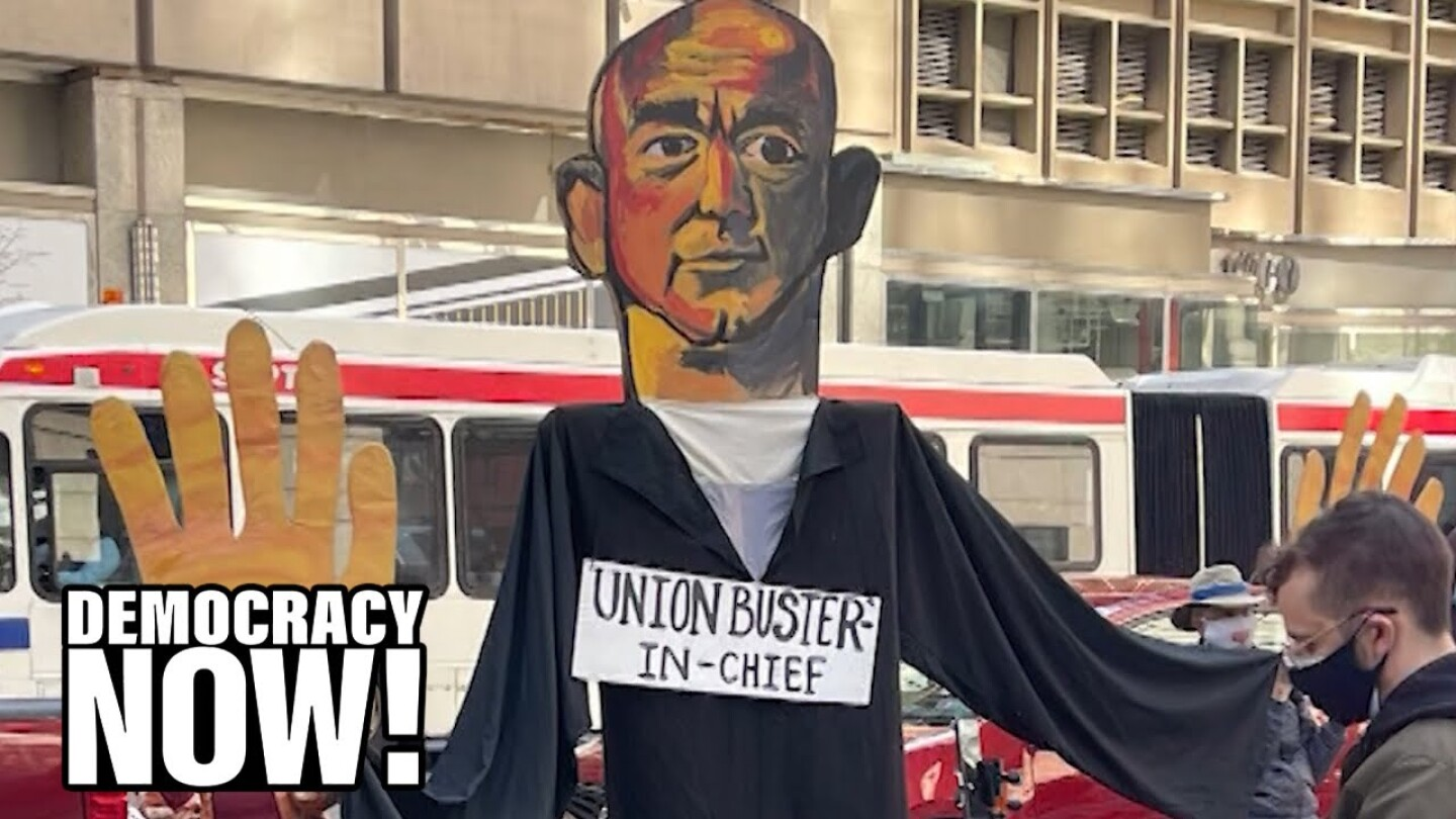 """A large cutout of Jeff Bezos with a sign on its chest saying """"Union Buster-In-Chief."""""""