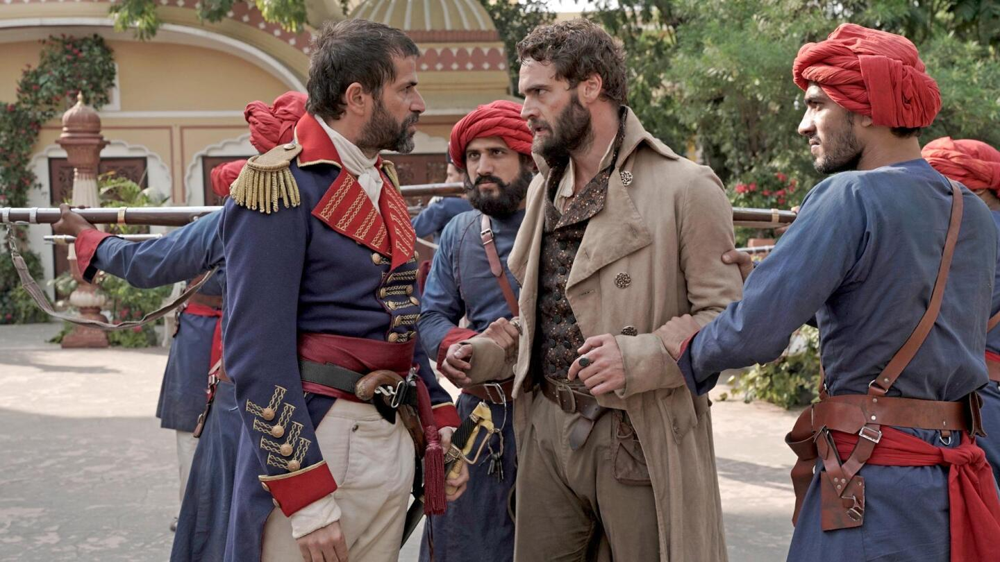 """John Beecham (Tom Bateman) is restrained and confronted by Indian police. 
