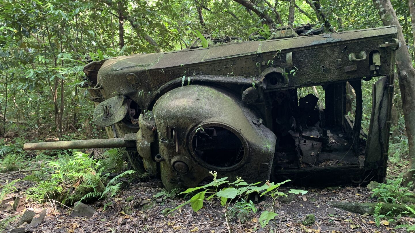 "A mossy, old war vehicle overturned in the forest. | ""1st to Fight: Pacific War Marines"""