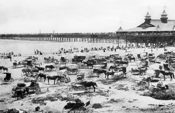 Horses and carriages on the beach near the Long Beach Pier, circa 1900.