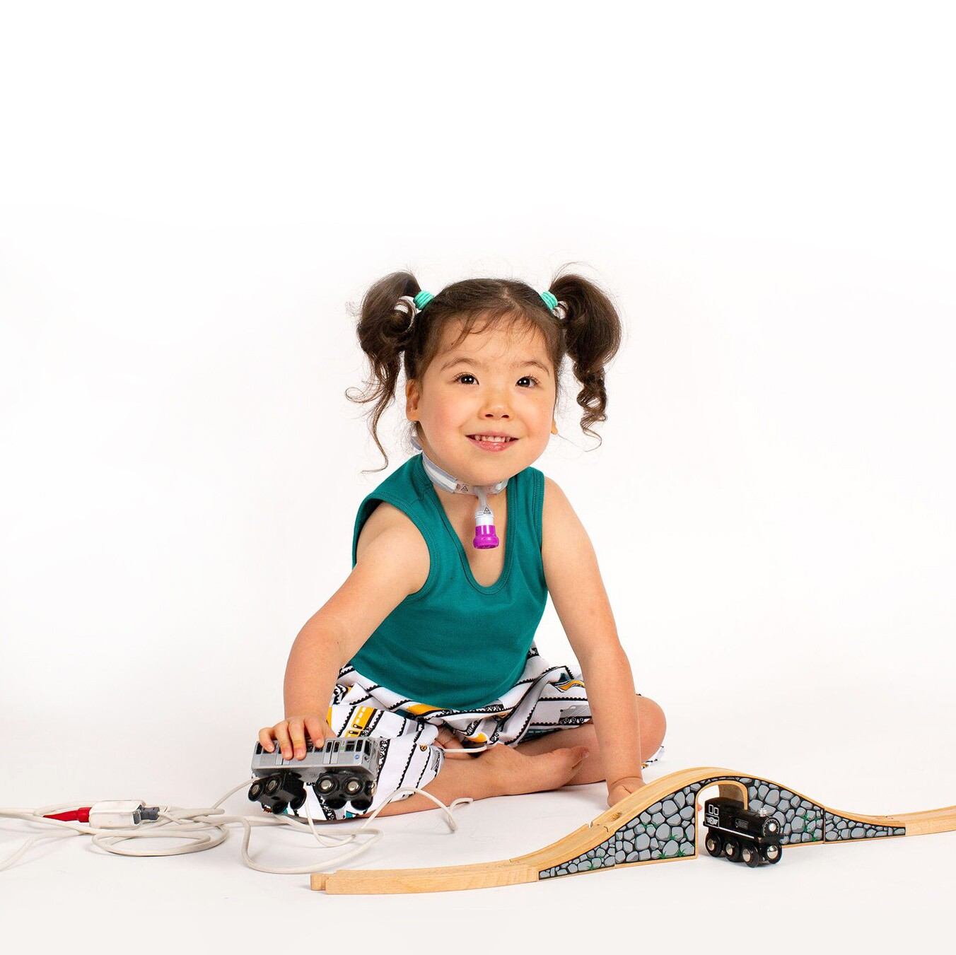 A young girl with a tracheostomy tube playing with trains
