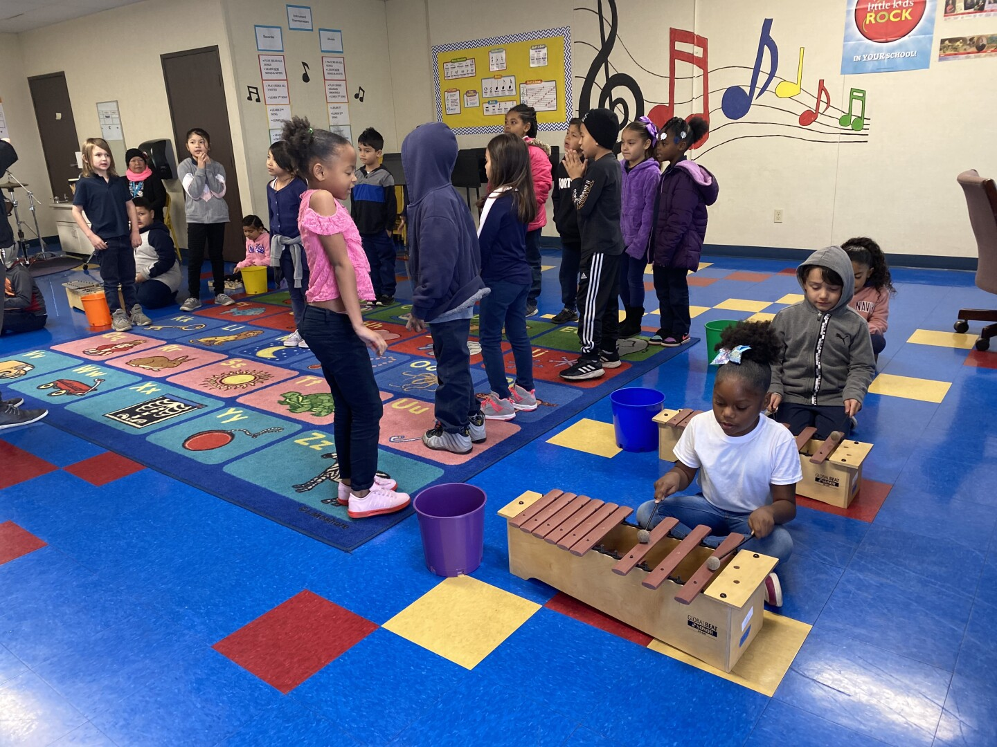 Students assemble in a classroom with some lining up while others play music on a xylophone.