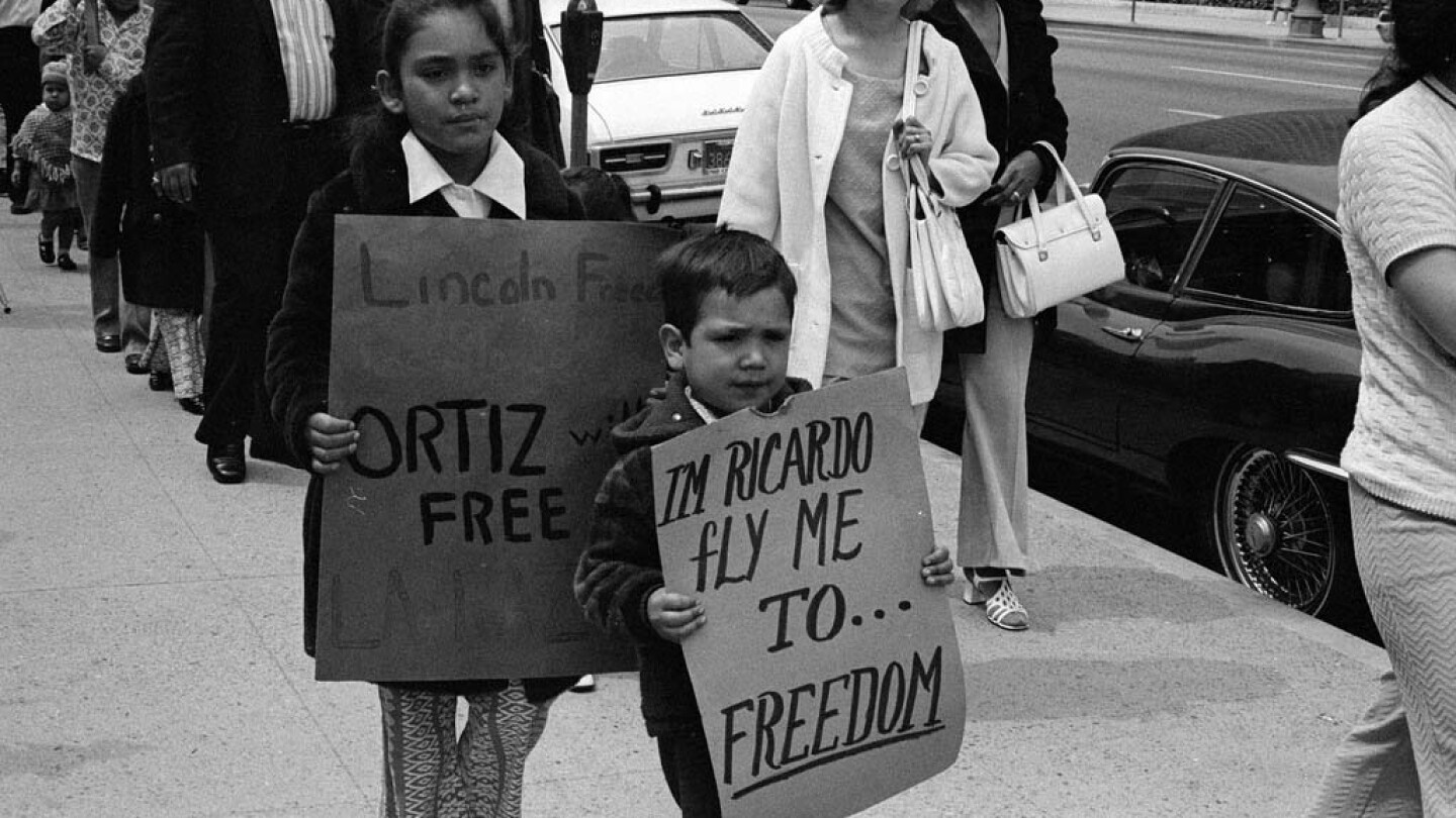 CSRC_LaRaza_B17F22S6_N007 Children carrying signs in support of Ricardo Chavez Ortiz in downtown Los Angeles | Pedro Arias, La Raza photograph collection. Courtesy of UCLA Chicano Studies Research Center