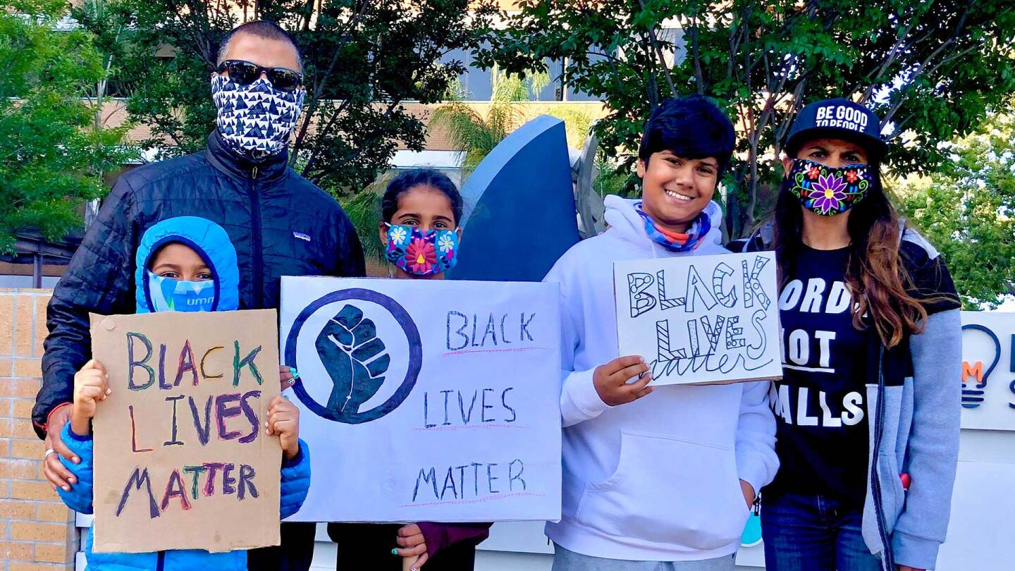 Aila Malik's family holds Black Lives Matter posters at a demonstration