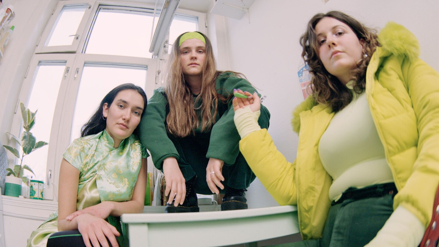 "Still from Sassy's ""Are You Leaving"": 3 Women in a white room, seen from a fish-eye perspective"