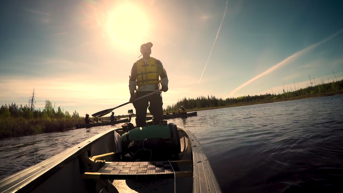 "A man stands in a canoe, looking over the water. | From ""La Loche"""
