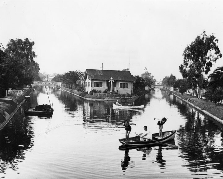 Two women dive into canals that are now paved roadways. Behind them is tiny United States Island. Courtesy of the Security Pacific National Bank Collection - Los Angeles Public Library.