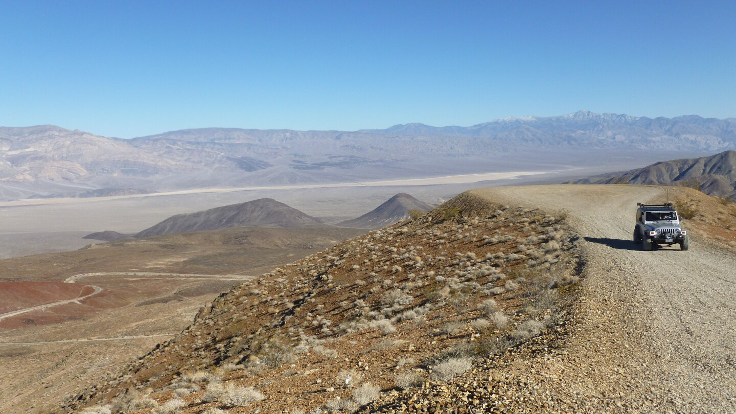A silver jeep sits on a dirt path with a wide view of Death Valley behind it.