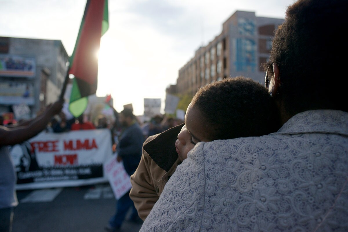 A parent holds a small child on their chest at a protest while the sun's rays shine on them.