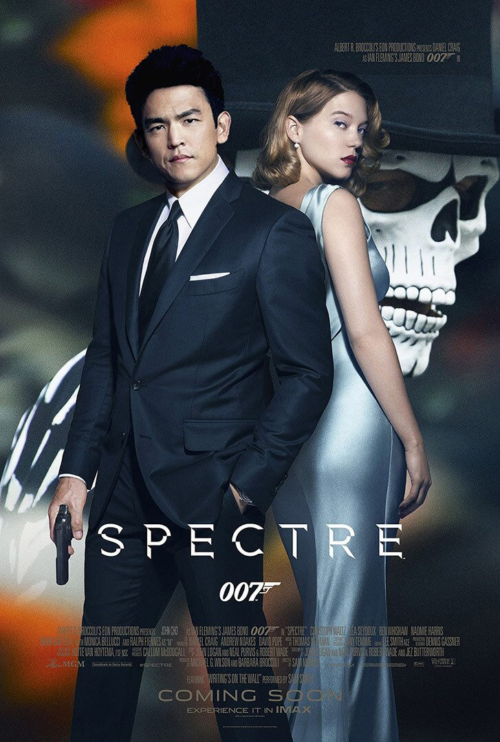 Movie poster featuring an Asian American with a gun in a suit standing in front of a blonde woman in an evening dress.