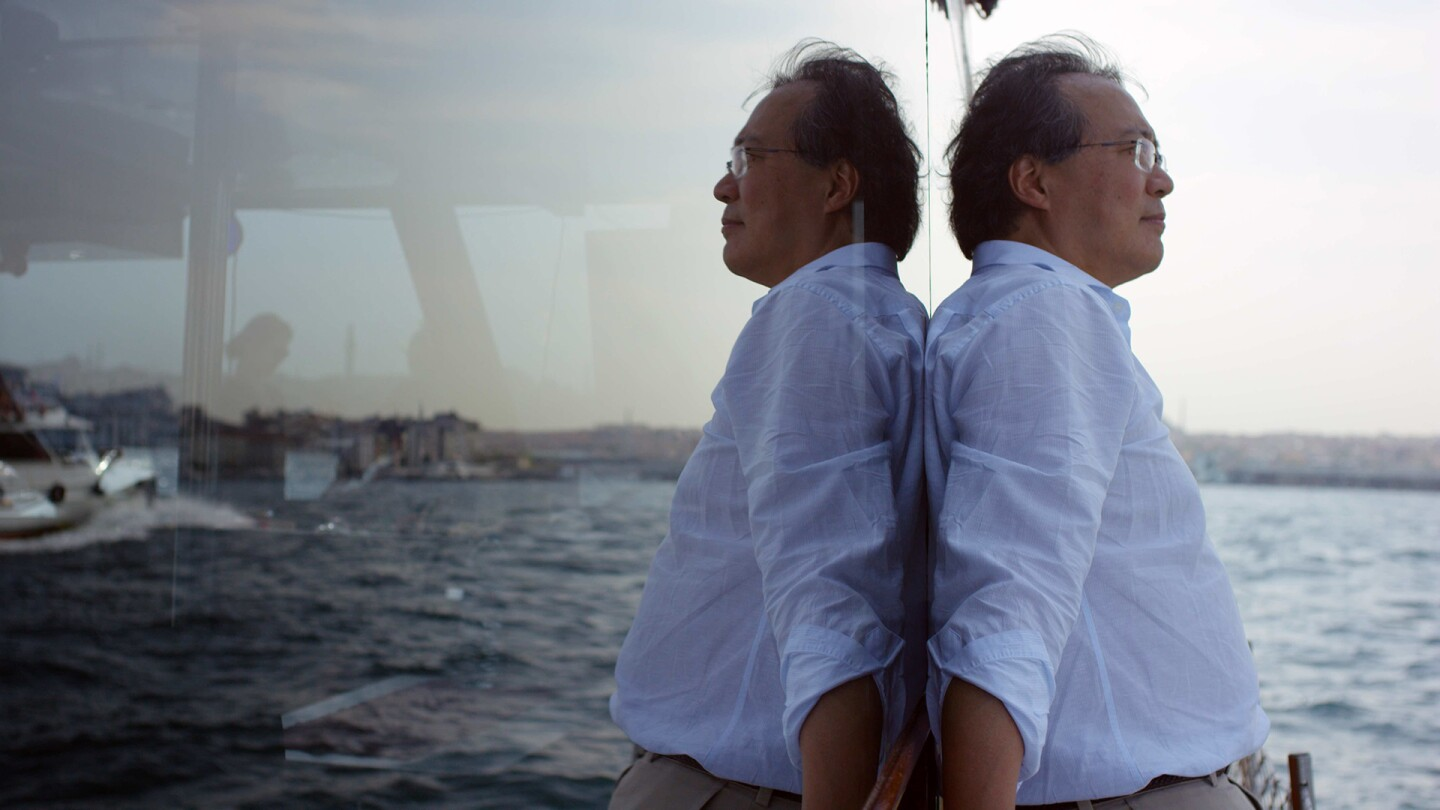 "Yo-Yo Ma leans against a wall of glass showing a reflection of the sea. | From ""The Music of Strangers"""