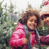 Two smiling children in puffy, colorful coats stand near snowy pine trees. istock
