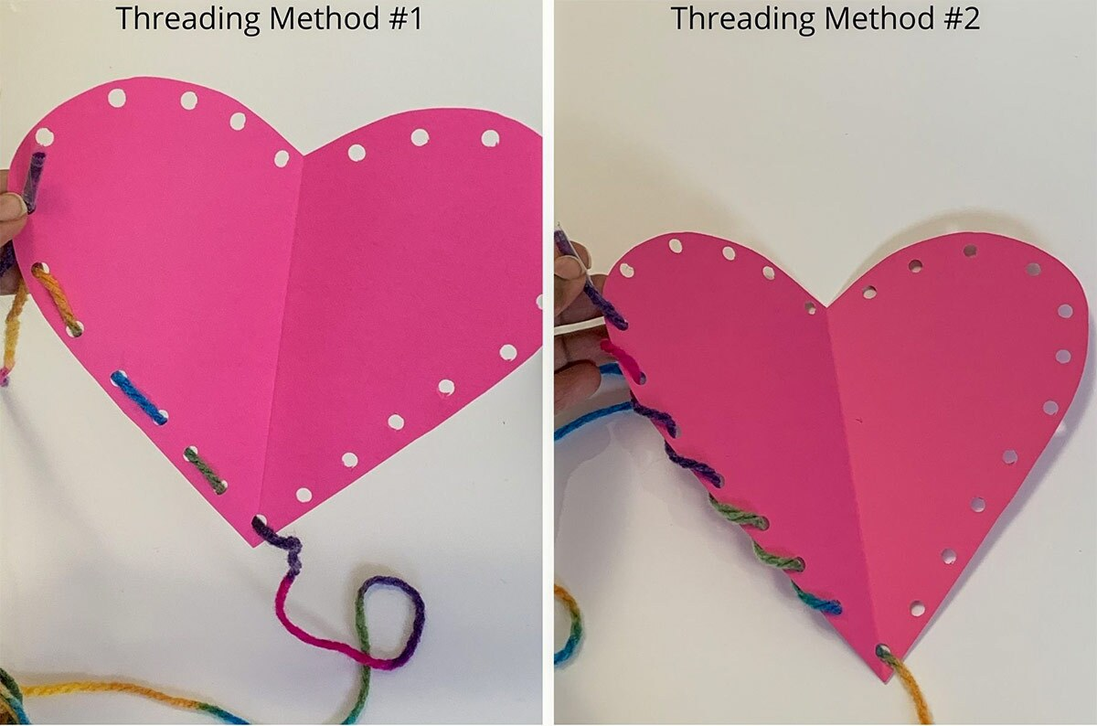 A pink paper heart craft gets threaded with yarn