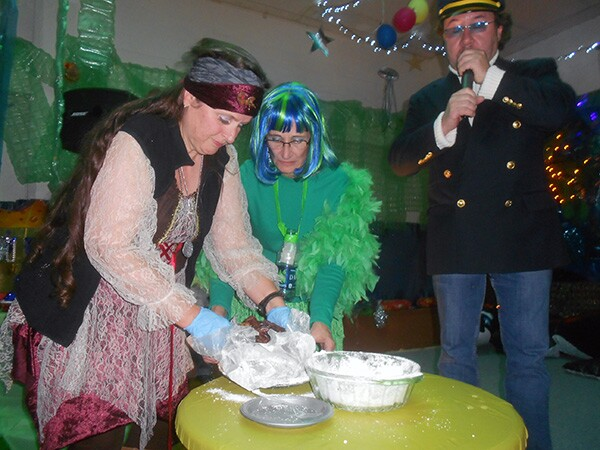 Fruitcake Festival organizers Mary Roper (left), Nancy Masters (center), and Michael Pietrobon (right) unveil the decade-old Archival Fruitcake as part of the event's annual rituals.