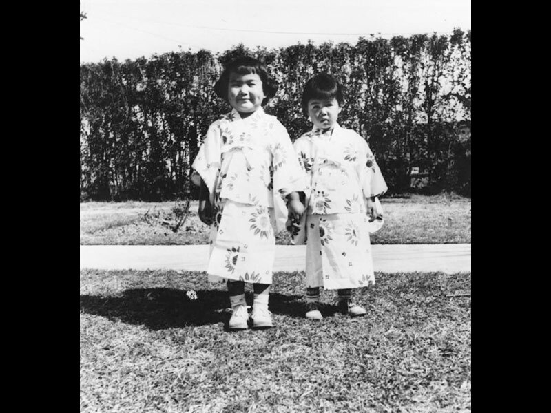Two Japanese American girls dressed in kimonos stand side by side, 1962