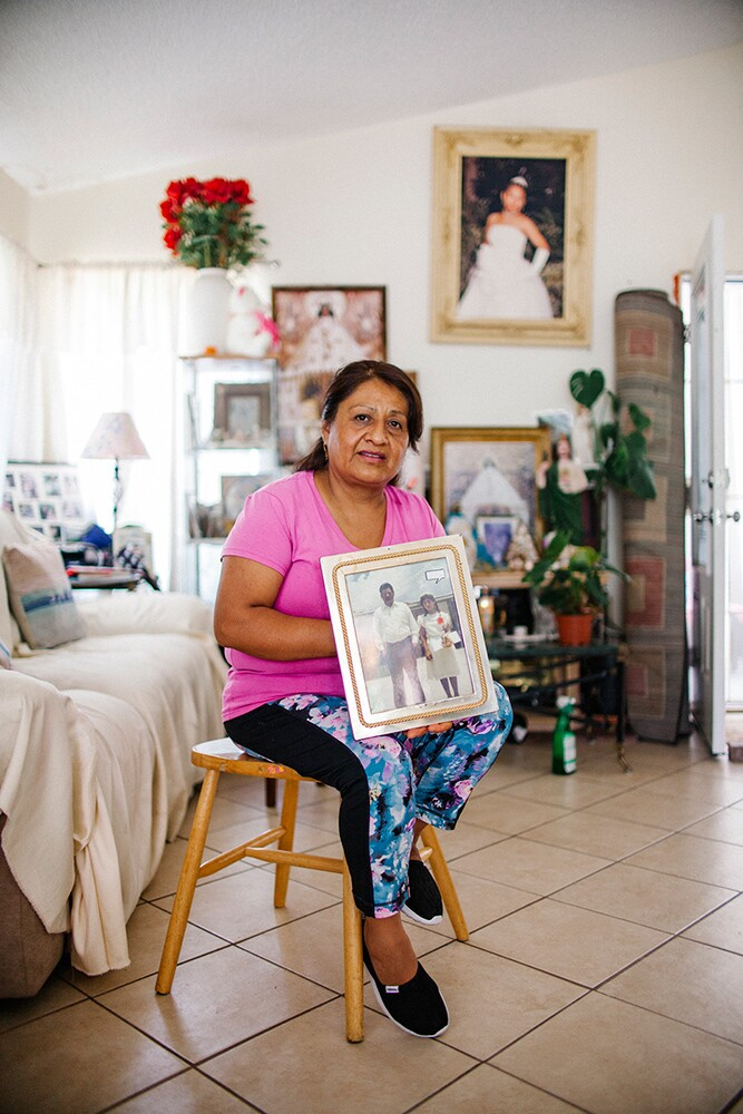 Reyna Garcia at home with a family photo. | Samanta Helou Hernandez