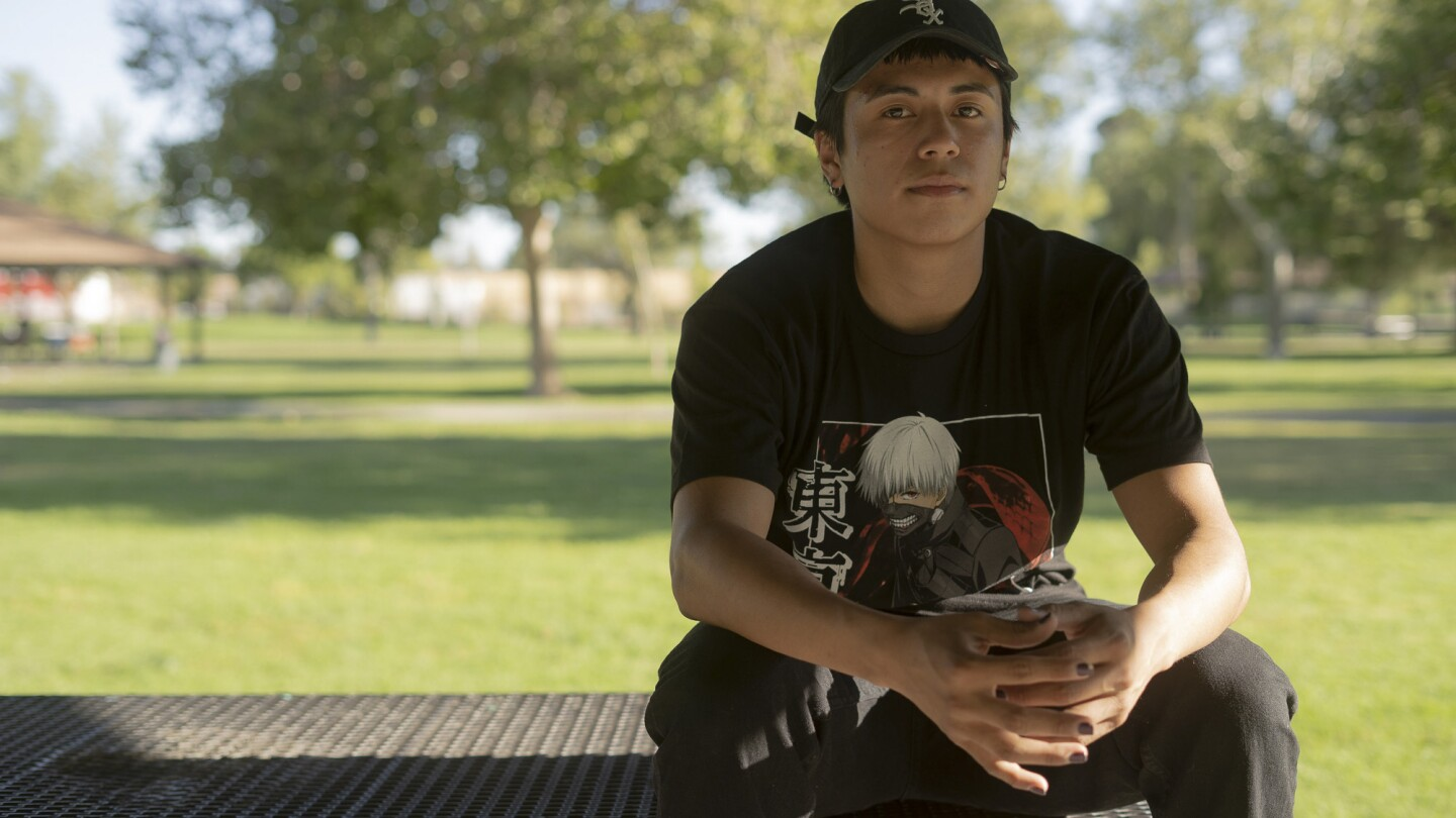 A young olive-skinned person wearing a black cap, grey painted nails and a black t-shirt with an Anime character on it looks at the camera with a very slight smile. He is sitting on top of a table at a park.
