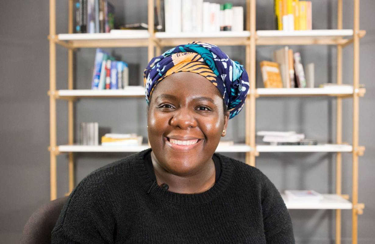 A Black woman wearing a black shirt and blue hair wrap smiles at the camera.