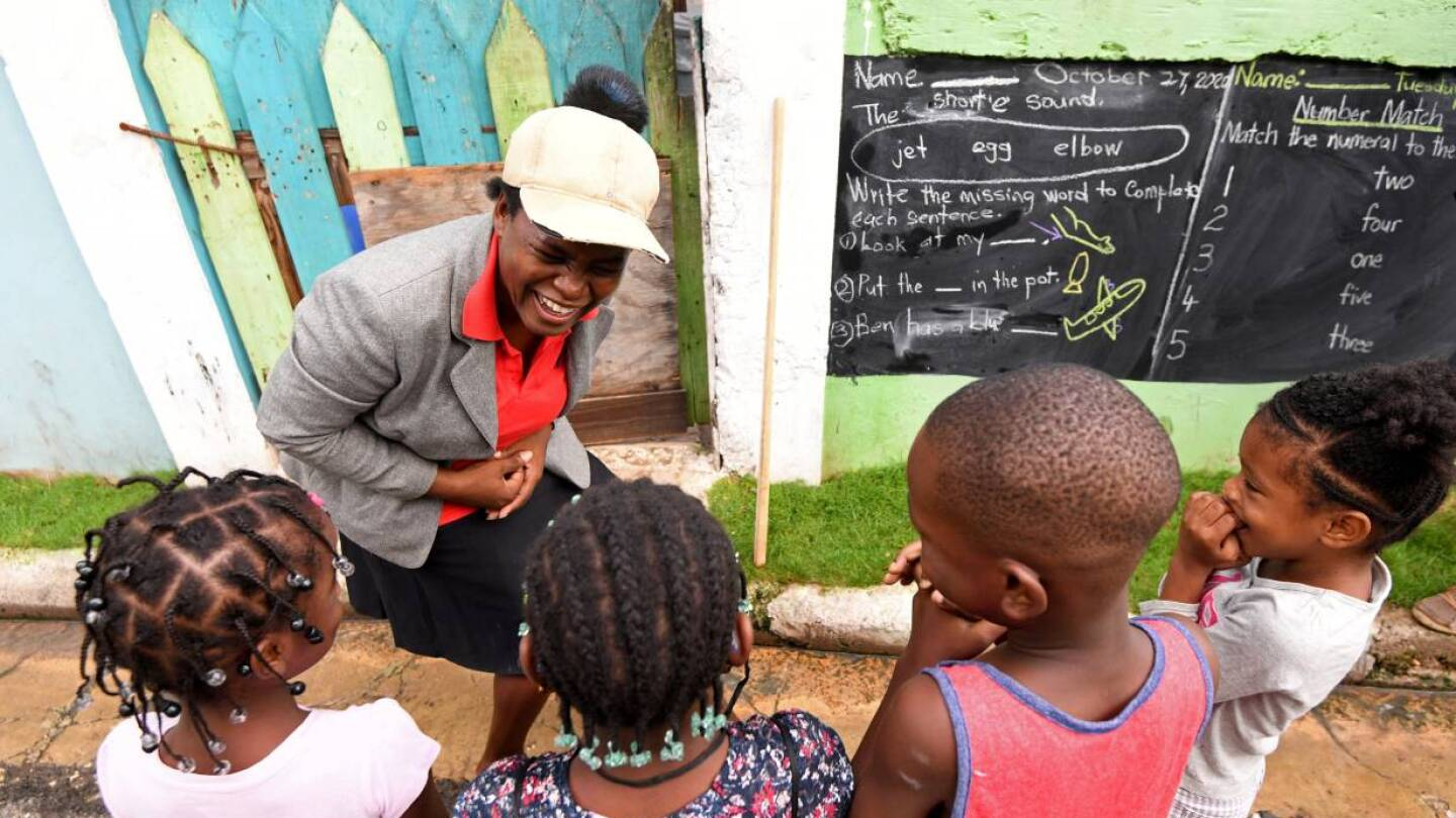 Educator Taneka Mckoy Phipps teaches a lesson with a blackboard painted on a wall, in a low-income neighborhood, during the coronavirus disease (COVID-19) outbreak in Kingston, Jamaica October 27, 2020. October 27, 2020. | REUTERS/Gladstone Taylor
