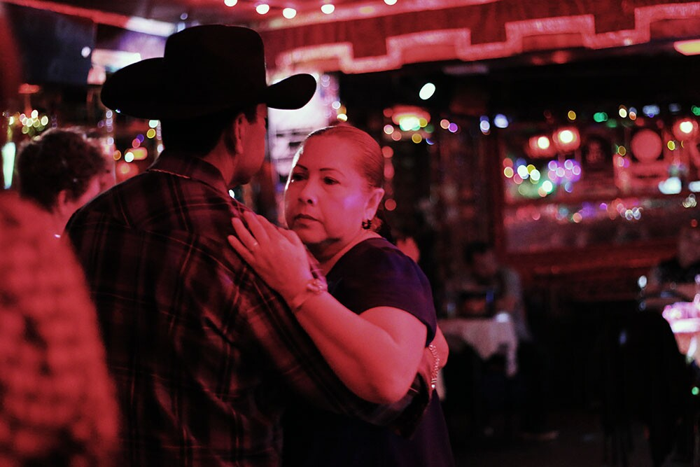 A woman and a man in a hat slow dance.
