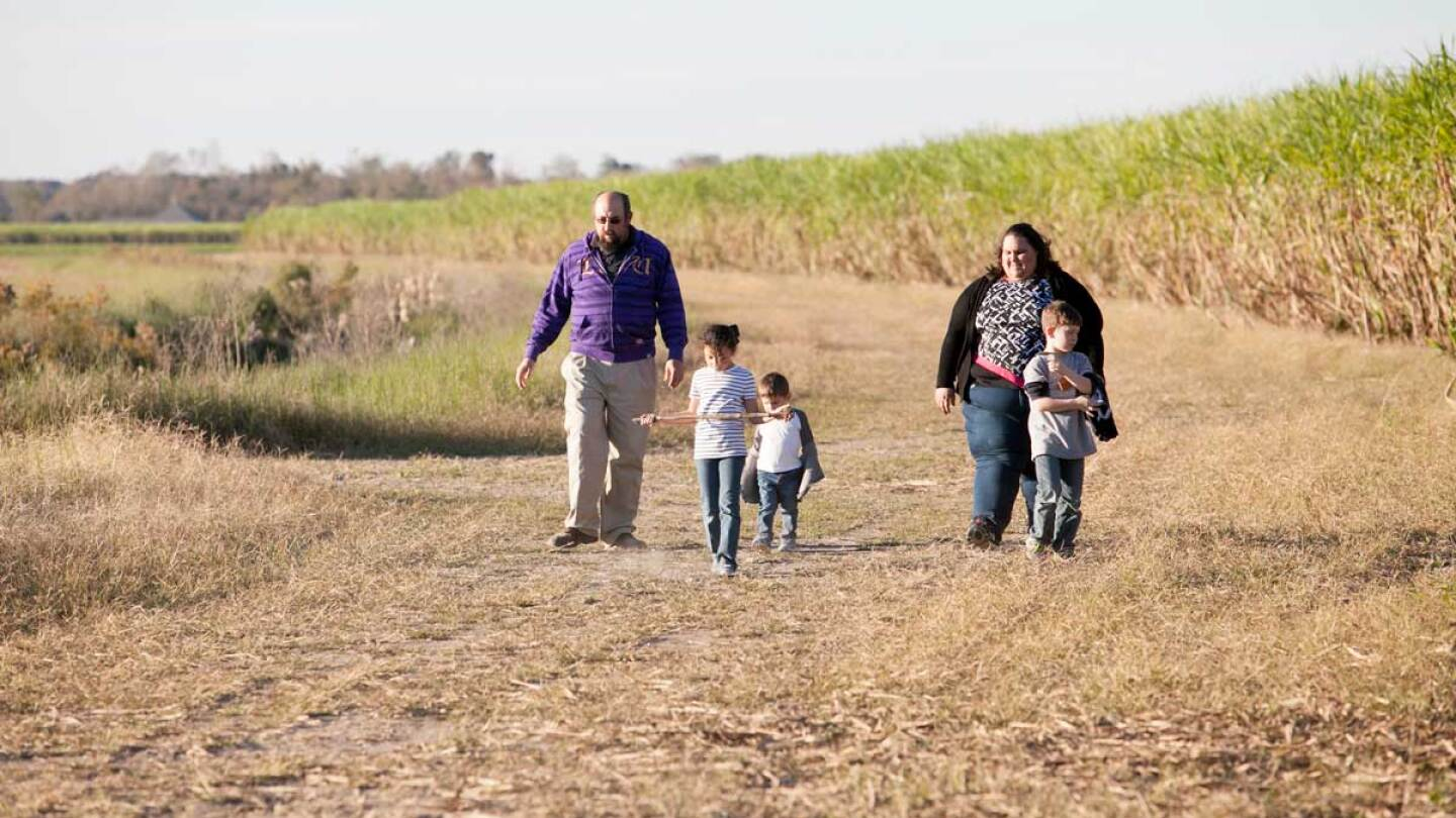 Chantelle Comardelle, the tribal executive secretary of theBiloxi-Chitimacha-Choctawband, walks with her family on the site destined for the tribe's relocation. | Nicky Milne/Thomson Reuters Foundation
