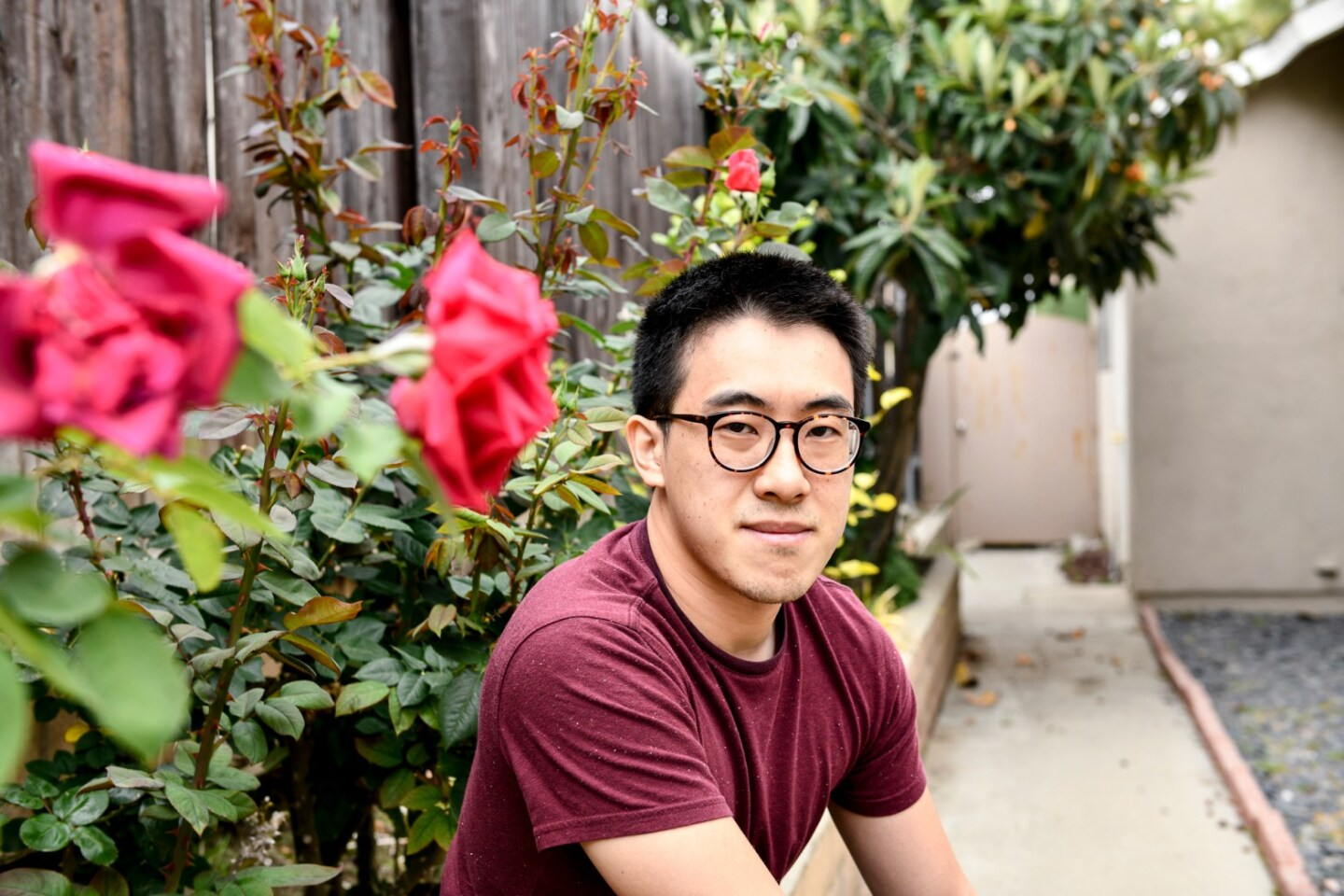 SF State graduate student Richard Lim poses for a portrait at his home in Rowland Heights on May 11, 2021.  He wears black glasses, a burgundy shirt and short black hair.