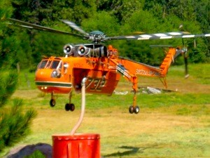 An Erickson Air-Crane refills its tank for more water drops.   Photo: Courtesy Inciweb