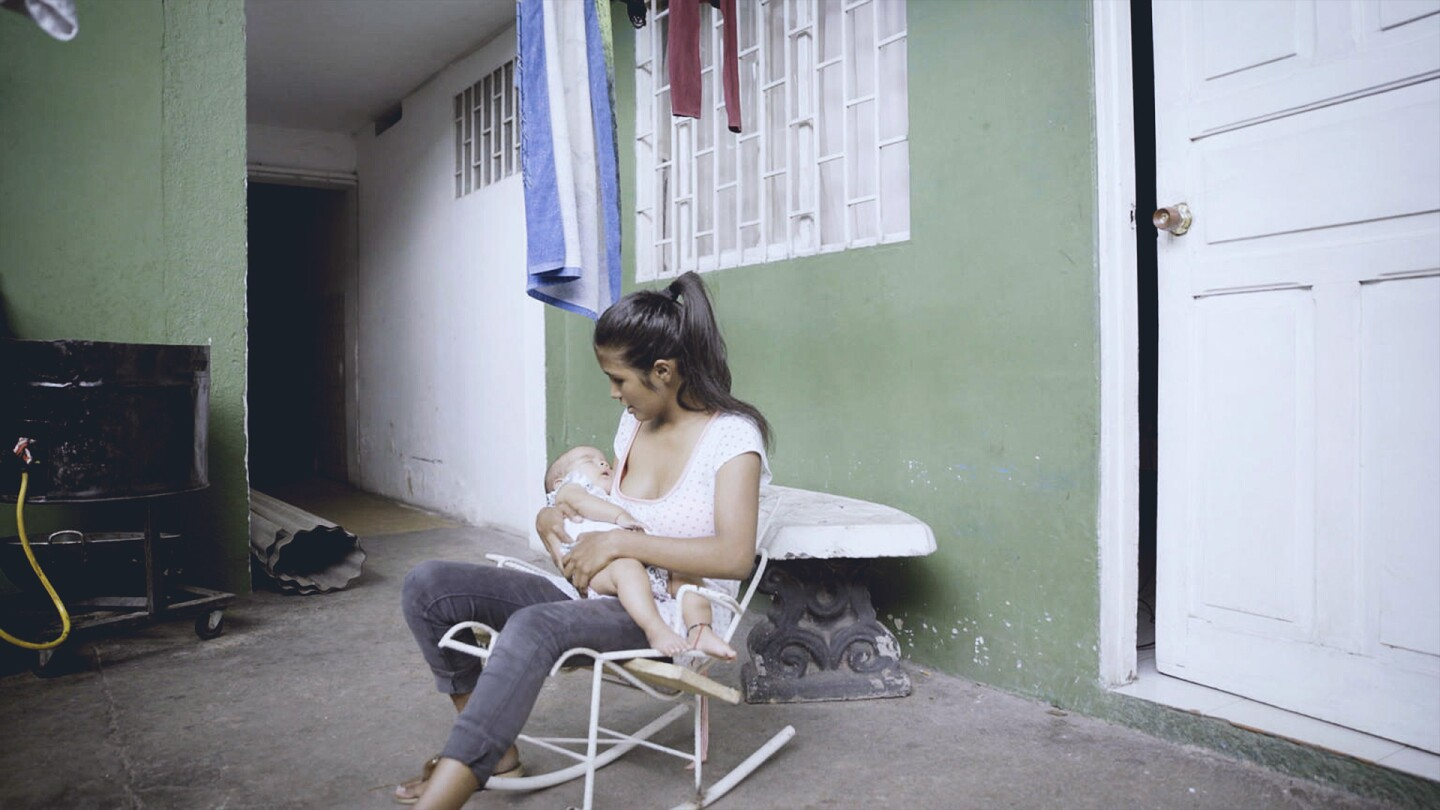 A woman holds an infant.