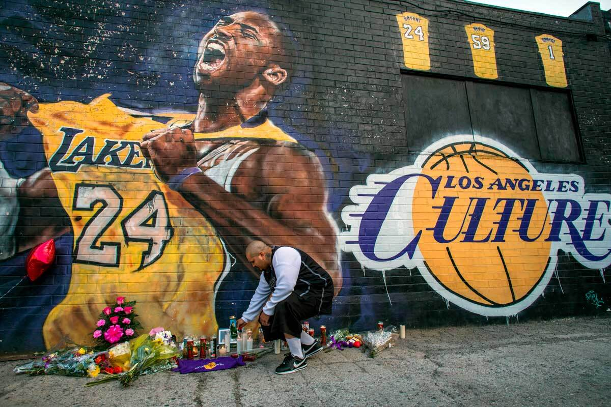 Luis Villanueva lights a candle in front of a Kobe Bryant mural in downtown Los Angeles on January 26, 2020 | APU GOMES/AFP via Getty Images