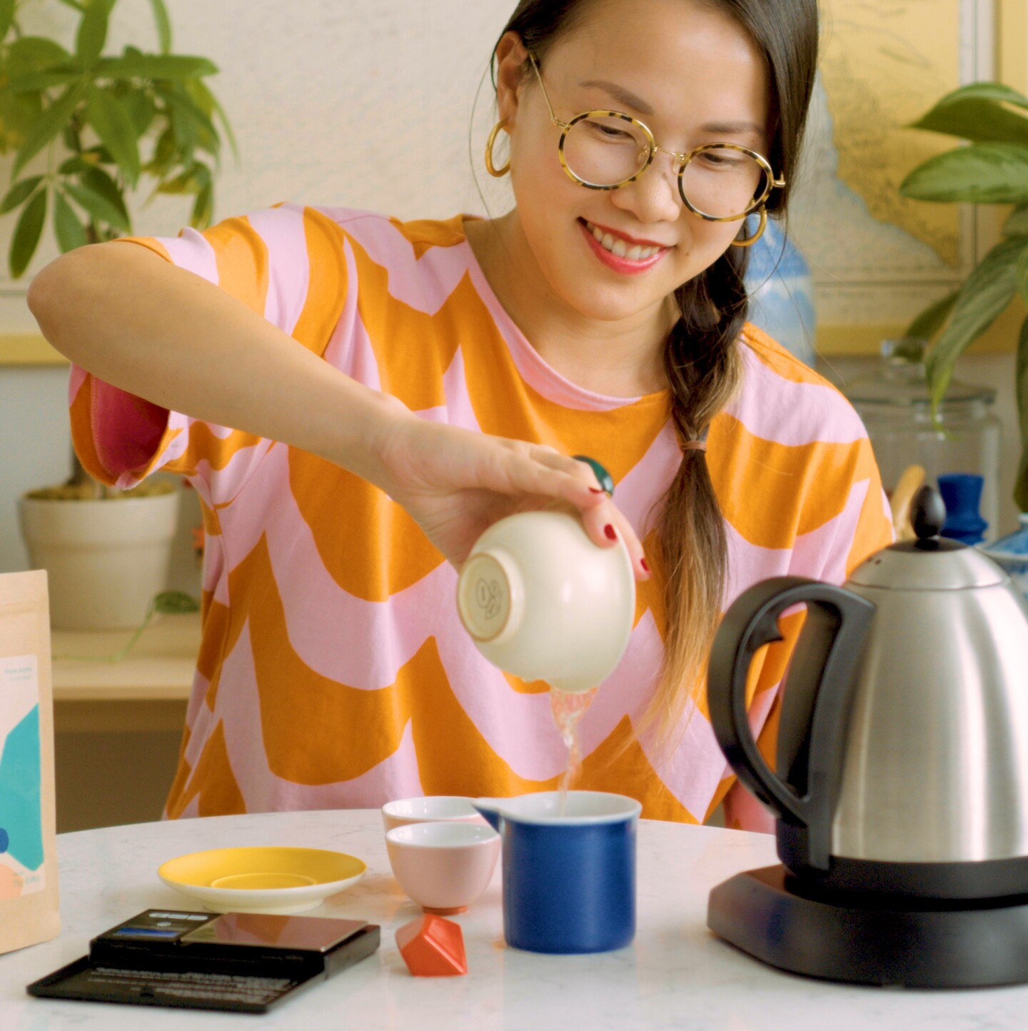 Diana Zheng pours hot water from a bowl into a cup to brew a Teochew dancong tea.