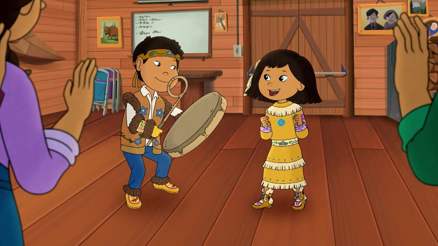 Cartoon of a little boy and girl in traditional clothing. The boy is playing a drum while the girl smiles.