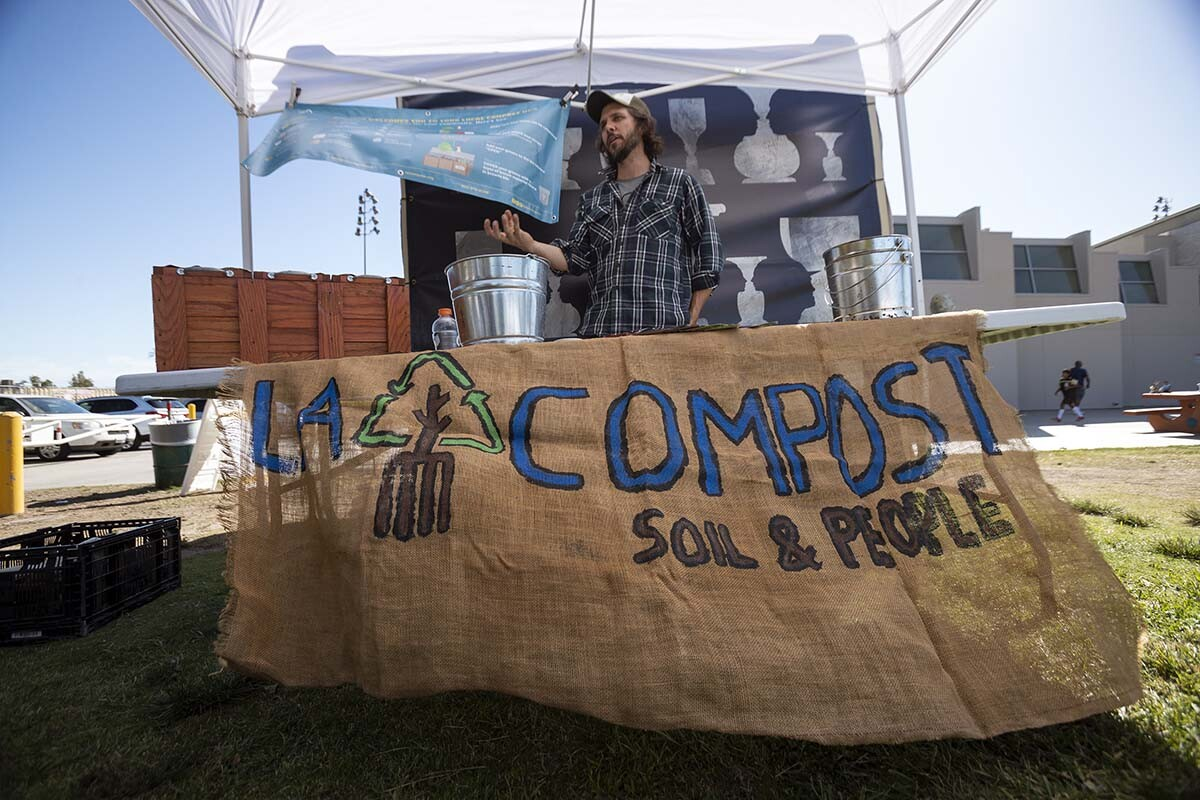 """A man stands behind a stall with the words """"L.A. Compost"""" while rehearsals of """"ALL AGAIN"""" go on."""