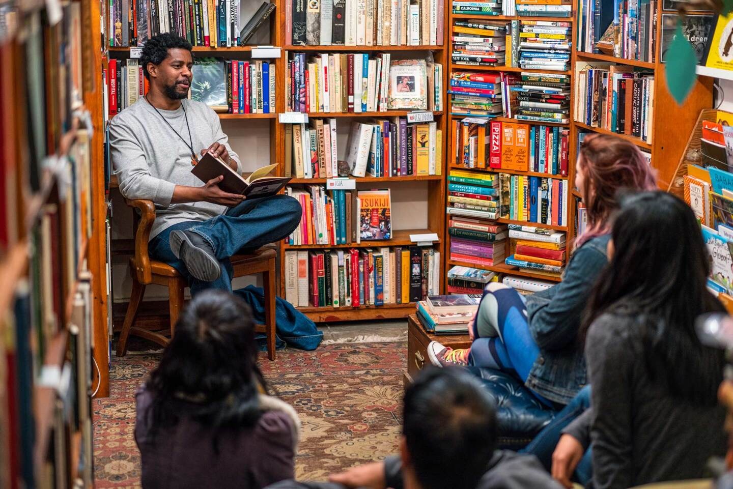 A man reads in a library to a group of people. | iStock