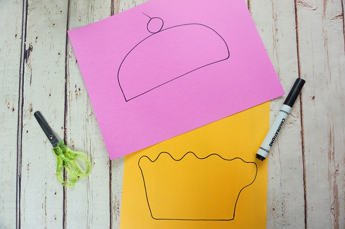 Two pieces of paper, one pink and one orange, with the top and bottom parts of a cupcake drawn on them.