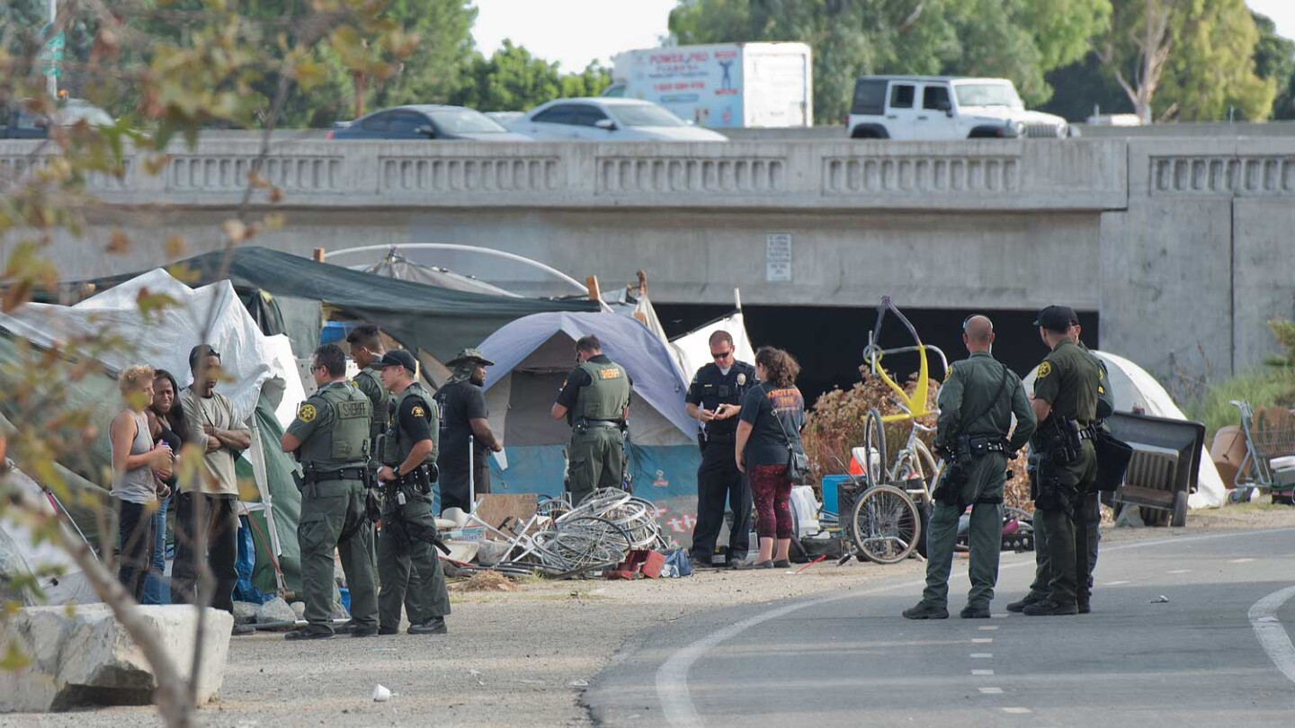 O.C. Sheriff's Deputies question residents of Santa Ana Riverbed homeless encampment.