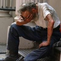 A homeless man sitting on a stoop | Ben Hershey / Unsplash