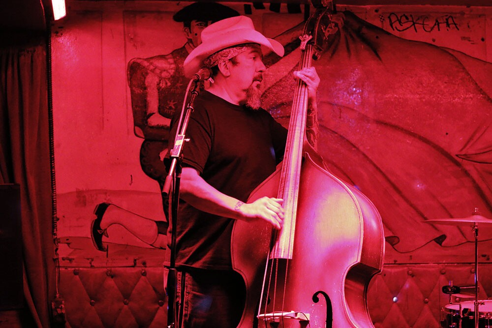 Double bass player with hat under a red light
